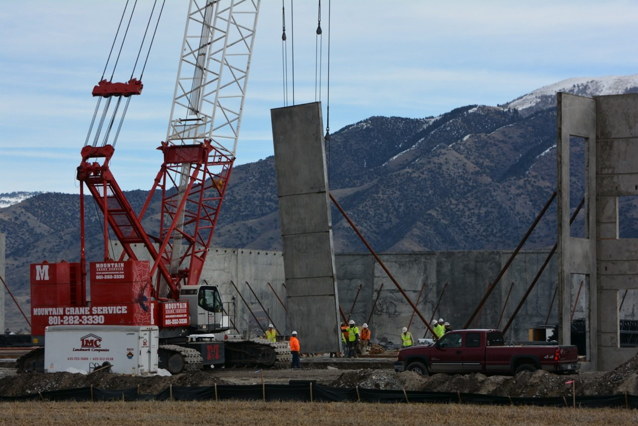 A crane lifts a concrete panel